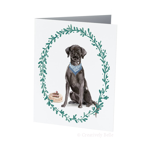 A perfect birthday card featuring a black labrador with a blue bandana by a bowl with birthday cake